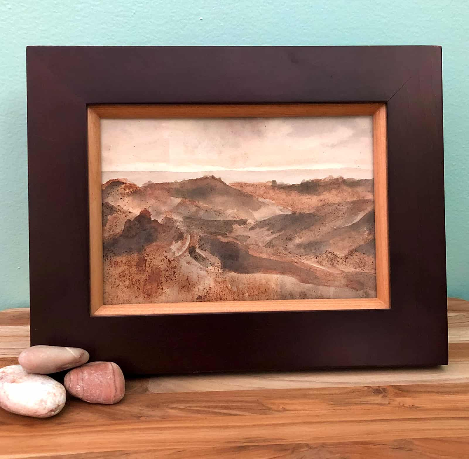 Framed cacao husk ink painting on shelf display